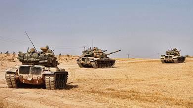 جنود أتراك يقودون دبابات أمريكية الصنع من طراز M60 في بلدة توخار ، شمال مدينة منبيج شمال سوريا امس