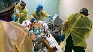 الاطباء يقومون بتركيب جهاز التنفس الصناعي لاحد المرضى