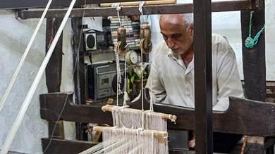 محمد سعود، ينسج خيوط الحرير على المنوال في ورشة منزله