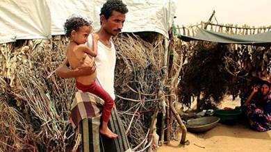 يمني يحمل طفلته في مخيم للنازحين (أ ف ب)