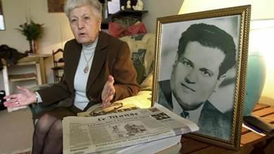 مليكة بومنجل أرملة المناضل الجزائري الراحل علي بومنجل تروي أمام صورته كيف قتل في حرب الحزائر في 1957 وذلك خلال مقابلة في منزلها