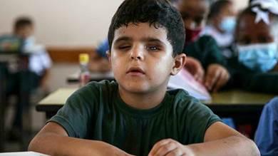 محمد شعبان بجانب زملائه خلال زيارته لمدرسته في بيت لاهيا شمال قطاع غزة