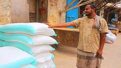 مواطن في لحج يقف أمام أكياس دقيق لمحل تجاري