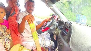 ياسر فوق باصه وعلى يده الخشبة الذي يستخدمها