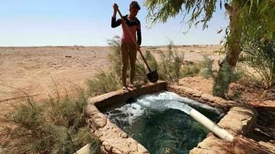 مزارع عراقي قرقب خزان مياه في حقل زراعي في قرية السحل بوادي حوران وسط محافظة الأنبار في 16 سبتمبر 2021
